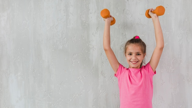 Ritratto di una ragazza sorridente che solleva le sue mani che tengono i dumbbells davanti al muro di cemento