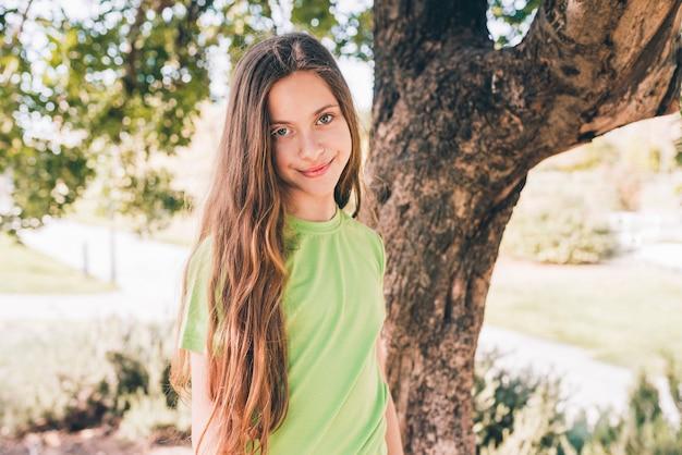Ritratto di una ragazza sorridente che sta davanti all'albero che guarda l'obbiettivo