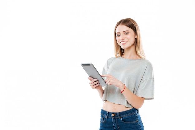 Ritratto di una ragazza sorridente che sta e che tocca il computer della compressa