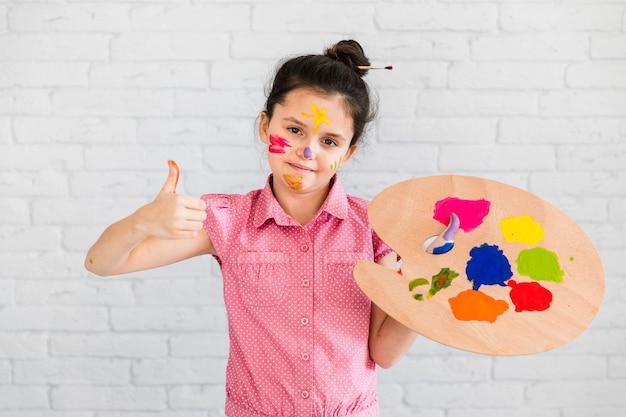 Ritratto di una ragazza sorridente che tiene multi tavolozza colorata che mostra pollice sul segno che sta contro il muro di mattoni bianco