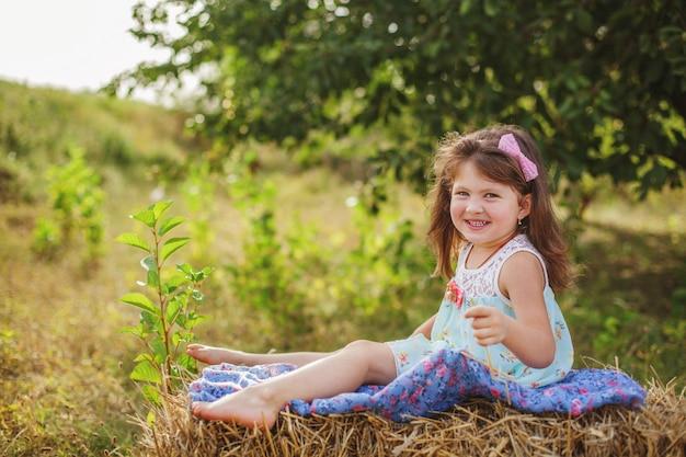 Ritratto di una ragazza sorridente con i capelli lunghi scuri seduto a piedi nudi su un pagliaio in estate