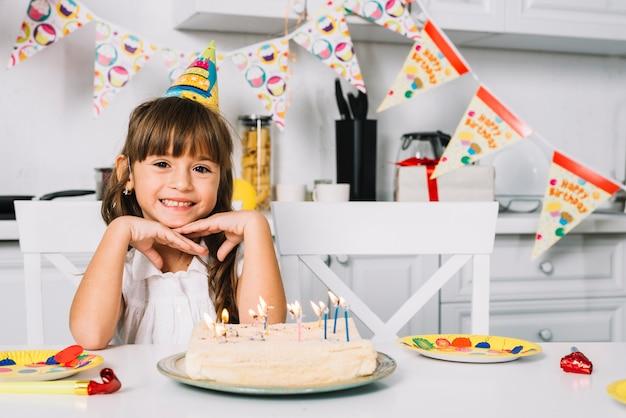 Ritratto di una ragazza sorridente di compleanno che si siede alla tabella con la torta di compleanno