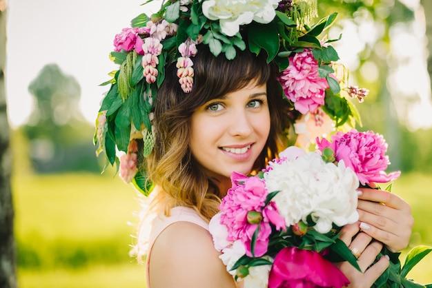 Ritratto di una ragazza sorridente felice con una corona di fiori e un mazzo di peonie