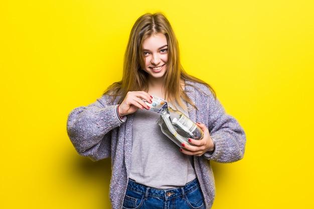 Ritratto di una ragazza teenager del brunette con i soldi del cuppingglass isolati. pentola con soldi nelle mani degli adolescenti
