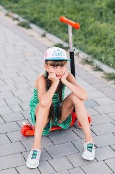 Ritratto di una ragazza triste che indossa tappo seduto sul motorino di spinta rosso