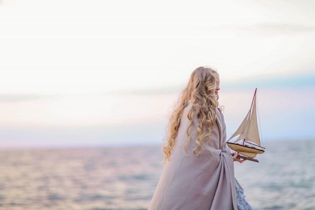 Ritratto di una ragazza vicino al mare seduto sulle rocce con una nave giocattolo nelle mani