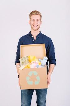 Ritratto di una scatola di cartone della tenuta dell'uomo in pieno di immondizia con l'icona di riciclaggio