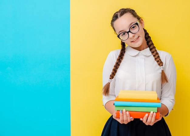 Ritratto di una scolara in vetri con i manuali dei libri sul blu giallo