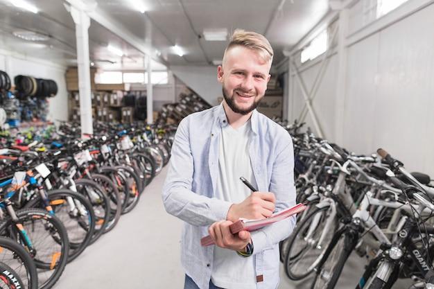 Ritratto di una scrittura felice dell'uomo sul documento nel negozio di biciclette