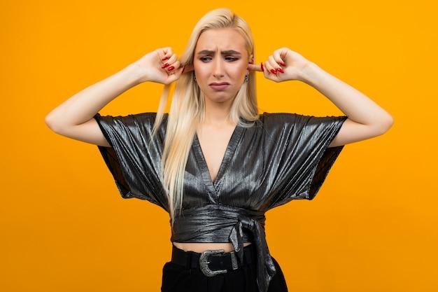Ritratto di una signora bionda che mostra malcontento coprendosi le orecchie con le mani sul muro giallo