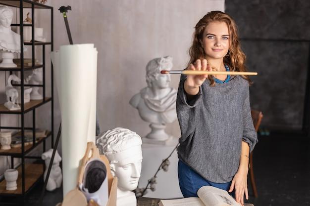 Ritratto di una splendida artista femminile che lavora al progetto artistico nel suo studio