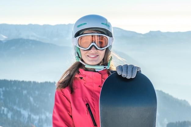 Ritratto di una sportiva che indossa casco e maschera con snowboard in mano guardando la fotocamera