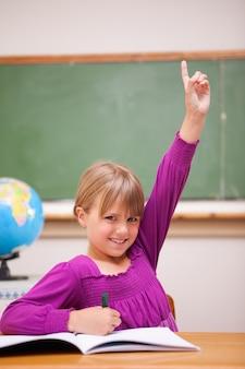 Ritratto di una studentessa alzando la mano