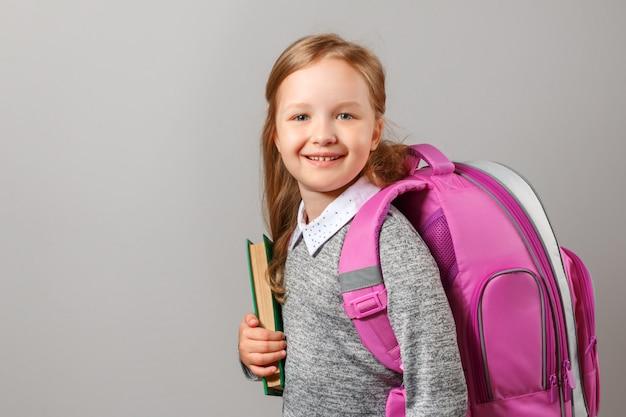 Ritratto di una studentessa bambina con uno zaino e un libro.