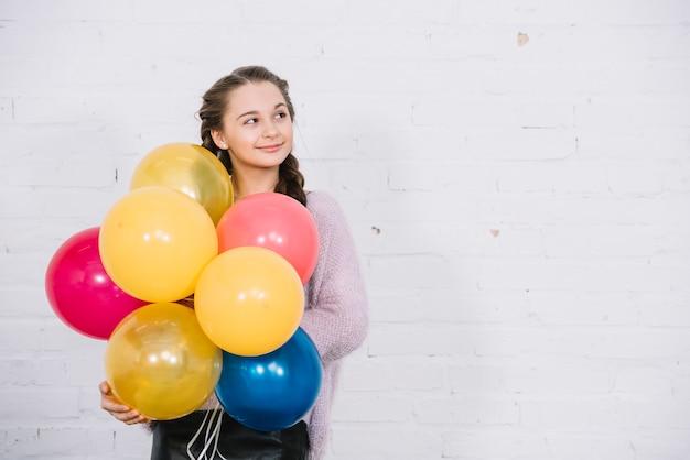 Ritratto di una tenuta adolescente palloncini in mano in piedi contro il muro bianco