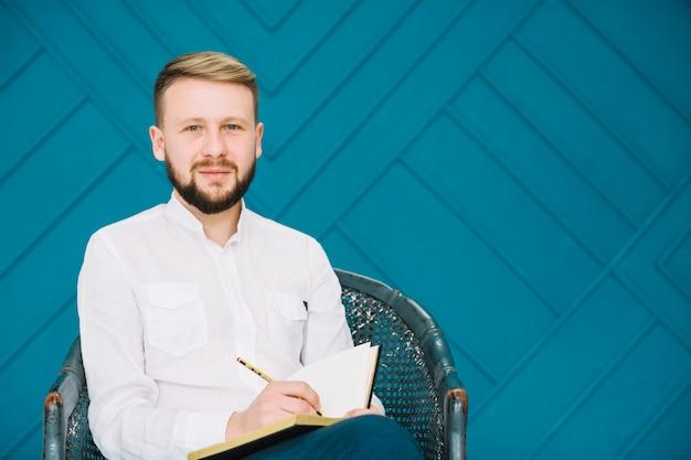 Ritratto di uno psicologo maschio che si siede sulla sedia che scrive nel diario con la matita che guarda l'obbiettivo