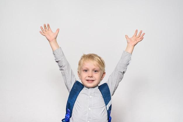 Ritratto di uno scolaro biondo allegro con una borsa di scuola