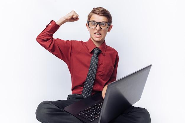 Ritratto di uno scolaro positivo ed emotivo in posa con un computer portatile