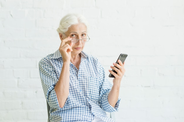 Ritratto di uno smartphone della holding della donna anziana davanti alla parete bianca