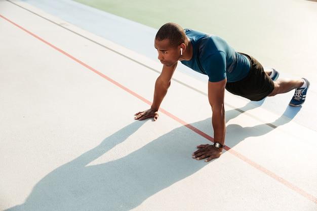Ritratto di uno sportivo afroamericano muscolare adatto che fa plancia