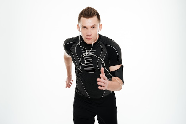 Ritratto di uno sportivo in buona salute che ascolta la musica mentre correndo