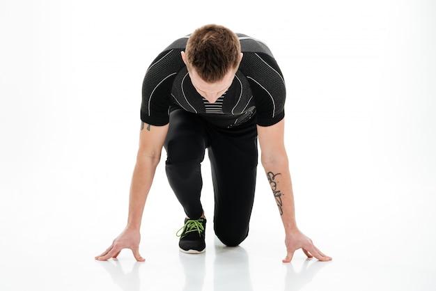 Ritratto di uno sprinter maschio concentrato che prepara iniziare a correre