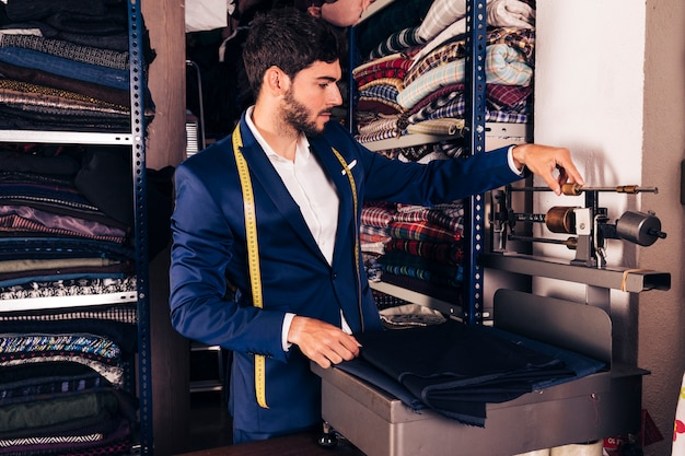 Ritratto di uno stilista maschio che regola la macchina della bilancia in tessuto nell'officina