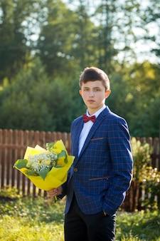 Ritratto di uno studente adolescente positivo, in un abito a righe blu, camicia bianca e farfalla rossa, si erge con un mazzo di rose gialle, all'aperto.