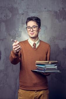 Ritratto di uno studente maschio con i libri del mucchio
