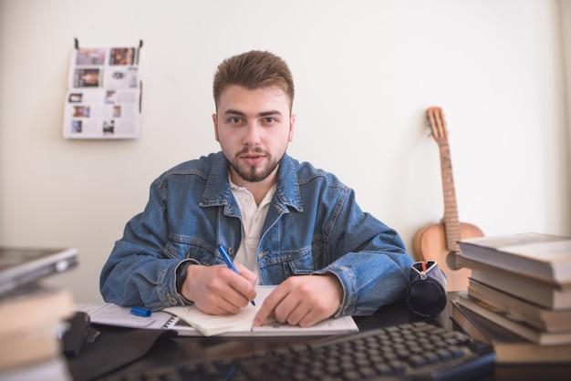 Ritratto di uno studente seduto a libri di testo, guardando un monitor di un computer e scrivere una penna