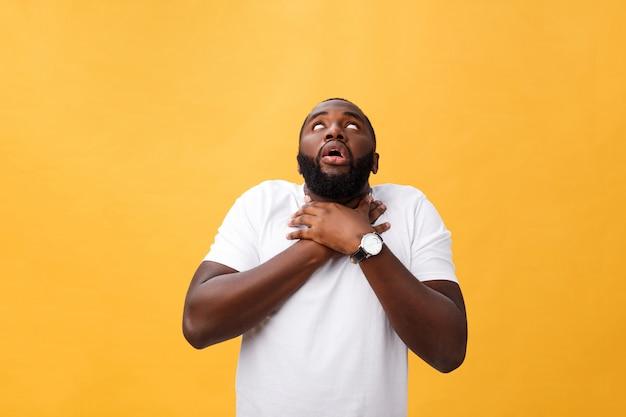 Ritratto di uomo afroamericano con le mani sollevate in stato di shock e incredulità. isolato su sfondo giallo.