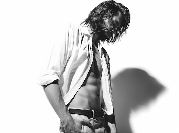 Ritratto di uomo alla moda hipster modello alla moda bello in camicia classica con petto nudo su bianco