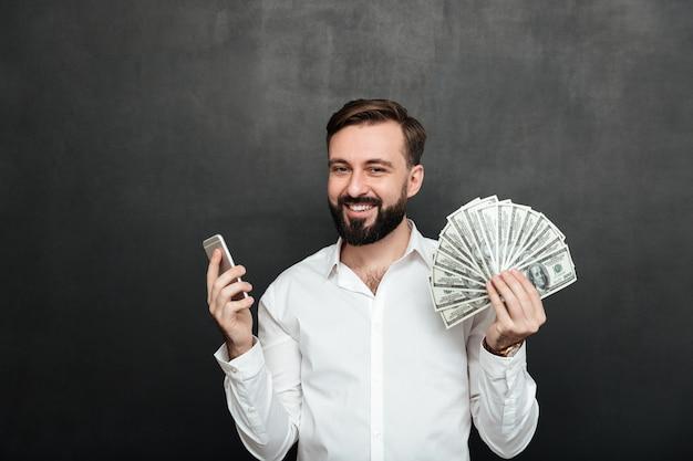 Ritratto di uomo allegro in camicia bianca vincendo un sacco di soldi in dollari valuta usando il suo smartphone, essendo gioioso su grigio scuro