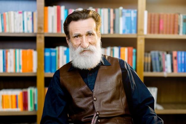 Ritratto di uomo anziano, bibliotecario o professore accademico, seduto sullo sfondo di librerie e scaffali nel mercato dei negozi di biblioteche o libri. giornata mondiale del libro felice, concetto delle biblioteche