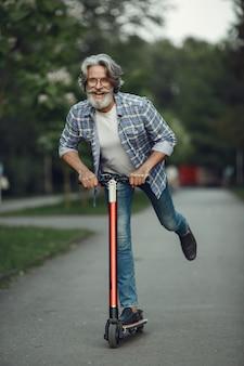 Ritratto di uomo anziano con kick scooter in un parco estivo