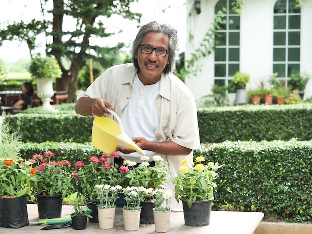 Ritratto di uomo anziano felice nel giardino fiorito