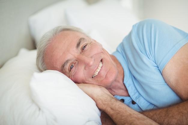 Ritratto di uomo anziano felice sdraiato sul letto