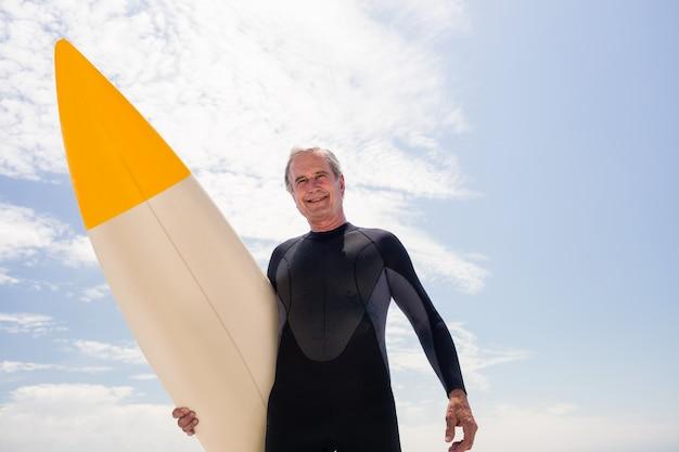 Ritratto di uomo anziano in muta tenendo una tavola da surf