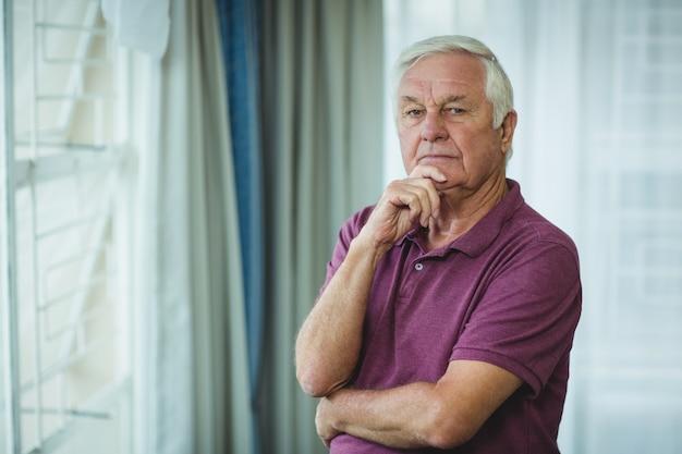 Ritratto di uomo anziano in piedi con la mano sul mento