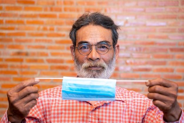 Ritratto di uomo anziano pronto a indossare una maschera protettiva per proteggere contro covid-19