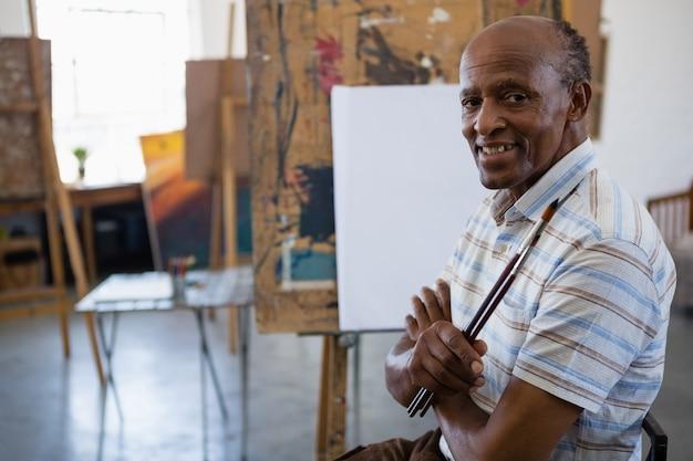 Ritratto di uomo anziano sorridente con le braccia incrociate