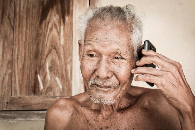 Ritratto di uomo anziano uso telefono, tono vintage