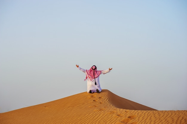 Ritratto di uomo arabo assetato in mezzo al deserto giallo.