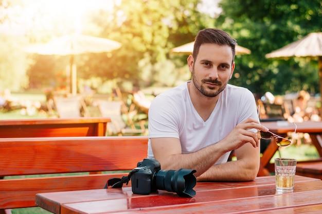 Ritratto di uomo attraente che si siede in street cafe