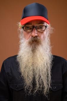 Ritratto di uomo barbuto anziano su colore marrone
