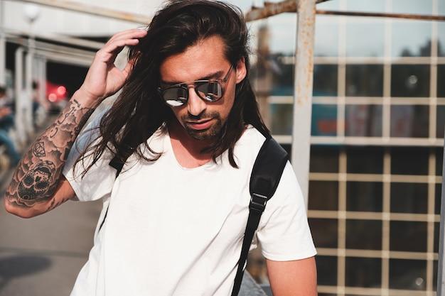 Ritratto di uomo barbuto attraente con occhiali da sole