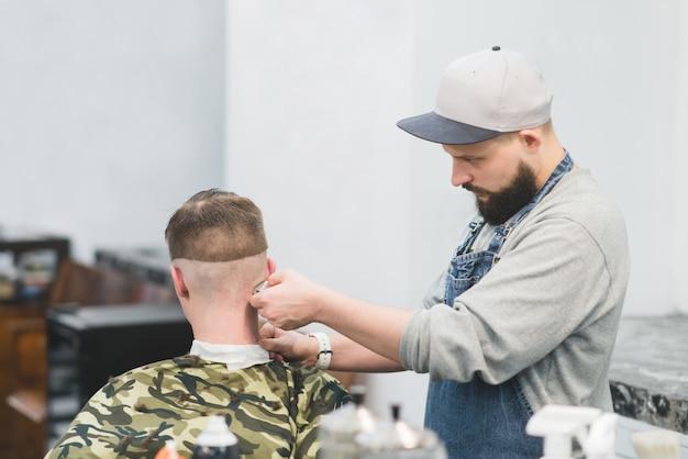 Ritratto di uomo barbuto barbiere al lavoro. crea acconciatura da uomo alla moda. il parrucchiere taglia il rifinitore del cliente