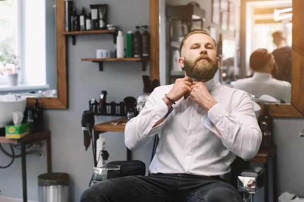 Ritratto di uomo barbuto bello con taglio di capelli alla moda e barba al negozio di barbiere.