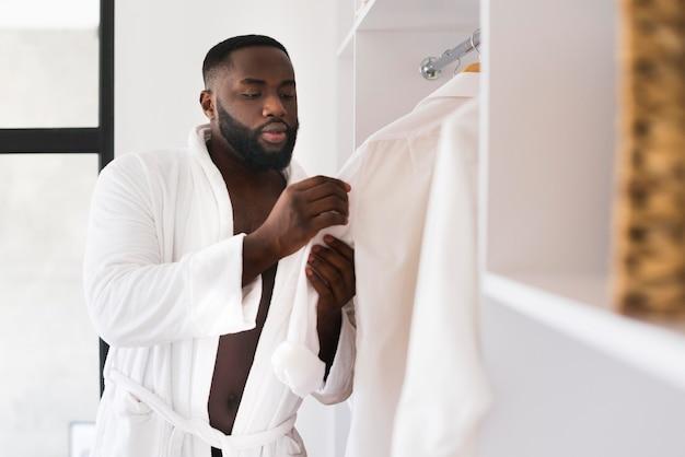 Ritratto di uomo barbuto che controlla il suo guardaroba