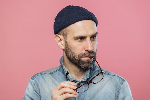 Ritratto di uomo barbuto pensoso si toglie gli occhiali, indossa giacca e cappello alla moda in denim